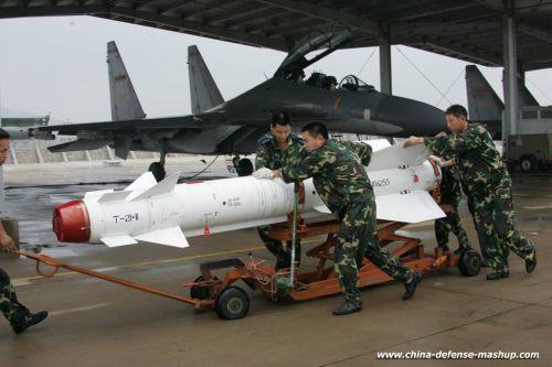 Personel AU Cina tengah mempersiapkan Kh-29TE dengan latar jet Sukhoi Su-30