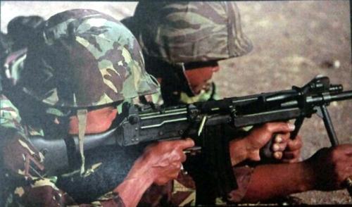 Dua prajurit Korps Marinir tengah mengoperasikan Ultimax, satu orang berperan memegangi dudukan bipod.