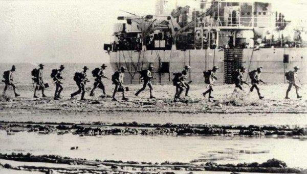 Pasukan TNI berjalan di pinggir pantai Dili, dengan latar KRI Teluk Bone.